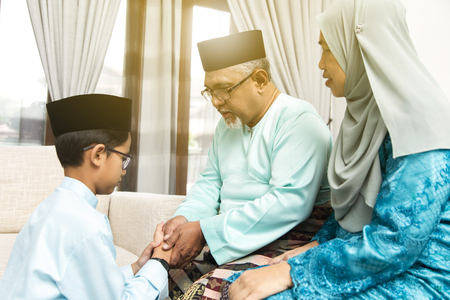 Traditional act of respect in Muslim family on Eid al-Fitr Standard-Bild