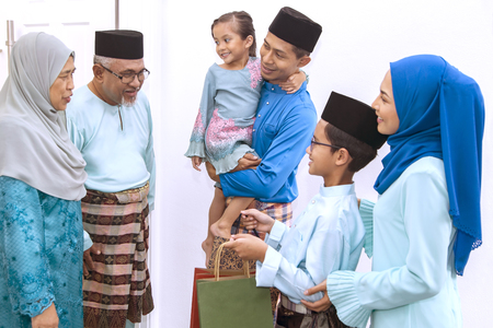 Muslim family visiting senior couple on Eid al-Fitr Stockfoto