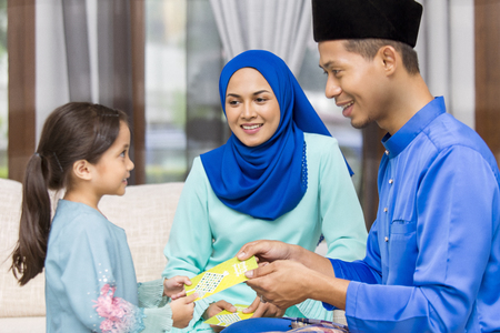 Muslim girl receiving green envelope from parents during Eid al-Fitr
