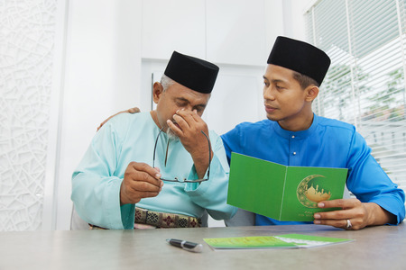 Muslim man comforting his father after reading a greeting card Фото со стока