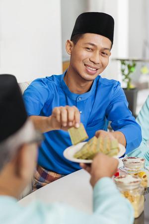 Muslim man holding traditional Malay layer cake