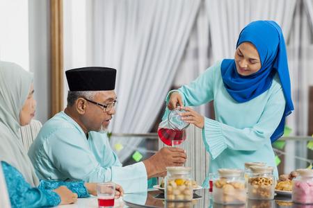 Muslim woman serving beverage to her parent Banque d'images