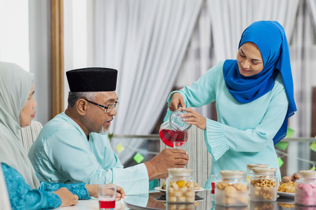 Muslim woman serving beverage to her parent Imagens