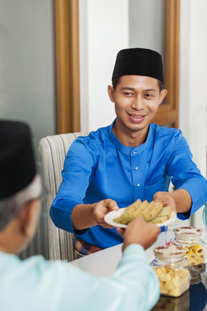 Muslim man serving food to his parent during Eid al-Fitr