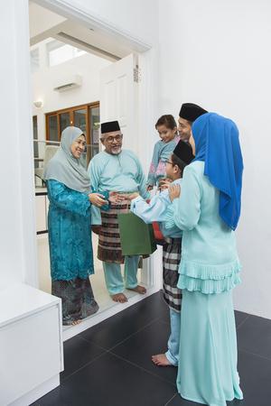 Muslim family visiting senior couple on Eid al-Fitr 写真素材