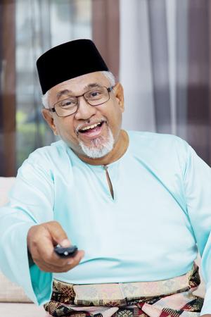 Senior Muslim man holding a remote control