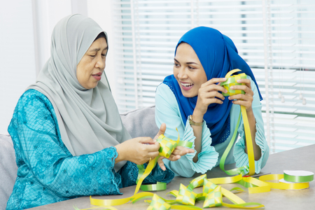 Muslim women weaving ribbon ketupats