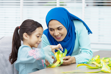 Muslim woman guiding her daughter in weaving ribbon ketupats