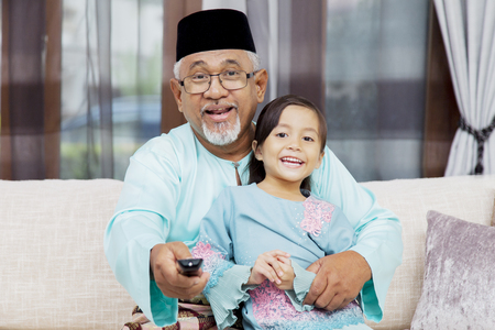 Senior Muslim man holding a remote control and his granddaughter