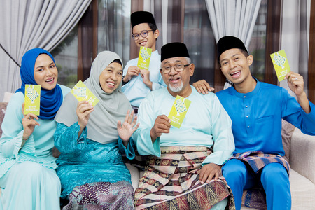 Muslim family with green envelopes Stock Photo