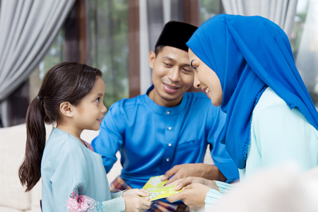 Muslim girl receiving green envelopes from parents during Eid al-Fitr