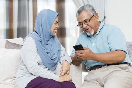 Senior couple checking the smartphone