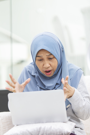 Senior woman is shocked looking at laptop screen
