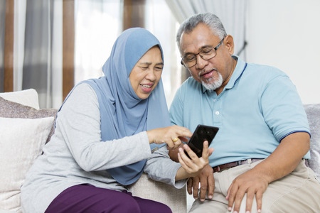 Senior woman showing husband something from the phone