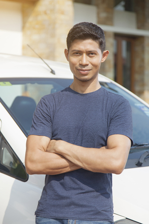 Mid adult man posing with his car