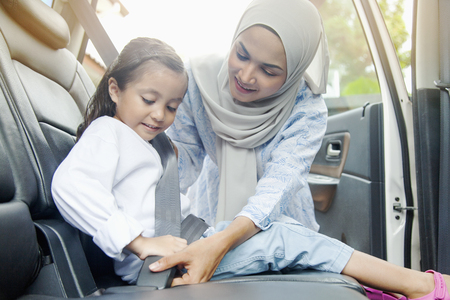 Mother putting on seat belt for her daughter