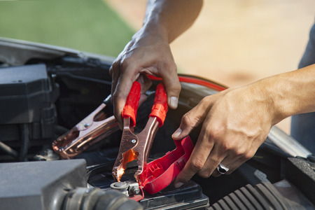 Man using battery jumper cables on a dead battery Stock Photo