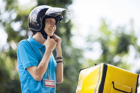 Food delivery man fastening helmet belt