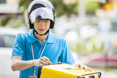 Food delivery man taking food from a bag Imagens
