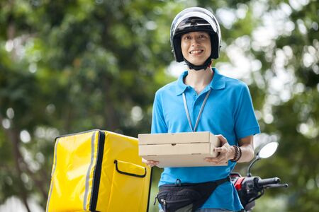 Delivery man carrying boxes of food
