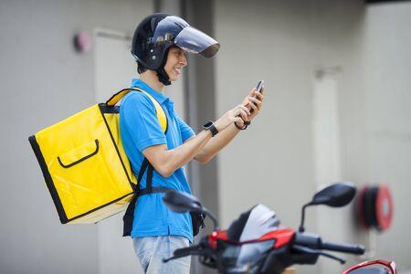 Lebensmittellieferant, der den Standort mit einem Mobiltelefon überprüft checking