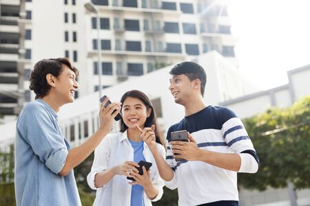 Three young adults using their smartphones Imagens