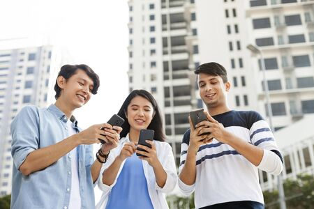 Three young adults using their smartphones Stock Photo