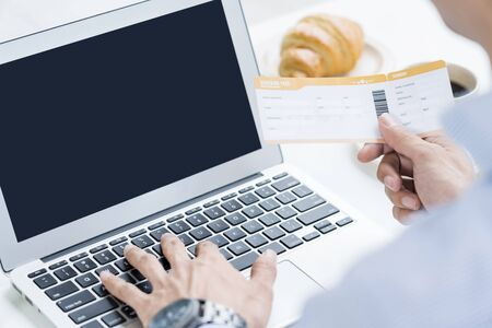 Man with boarding pass doing an online check in Banco de Imagens