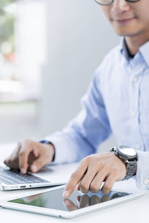 Man working with a laptop and a tablet computer