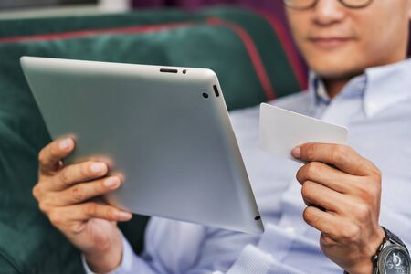 Man using a digital tablet on a couch