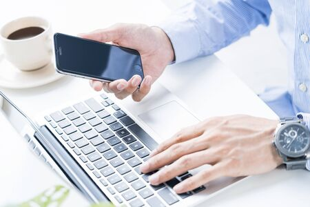 Man using a laptop and holding a smartphone