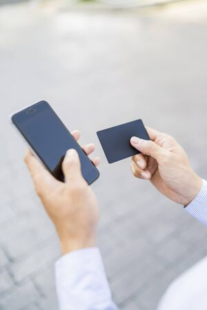 Man holding a phone and card