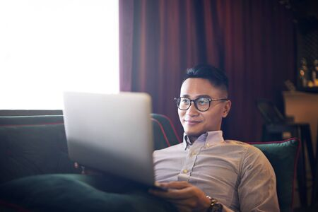Man using a laptop on a couch 免版税图像