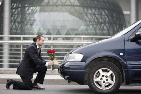 Businessman kneeling in front of a car, offering flowers photo