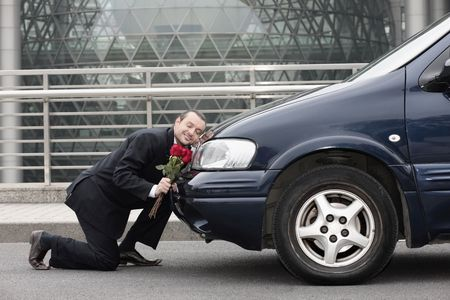 Businessman kneeling and resting his head on a car while holding flowers