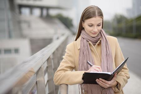 Businesswoman writing on an organizer photo