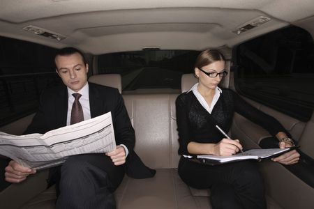 australian ethnicity: Businessman reading newspaper, businesswoman writing on an organizer in the car Stock Photo