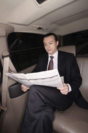 Businessman reading newspaper in the car photo