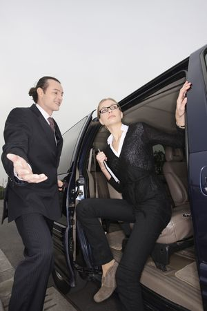 mpv: Businessman opening the car door, businesswoman getting out from the car Stock Photo