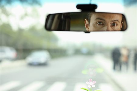 Businessman reflected in rear view mirror