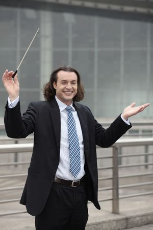 australian ethnicity: Businessman holding conductors baton Stock Photo