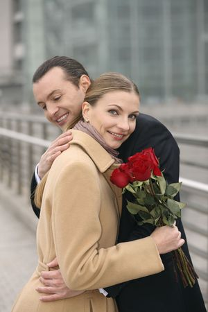 Businessman and businesswoman hugging, businesswoman holding flowers photo