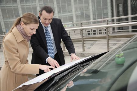 australian ethnicity: Businessman and businesswoman looking at map on hood of car Stock Photo