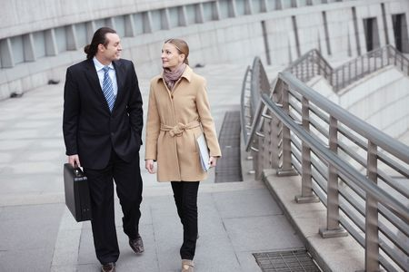 Businessman and businesswoman talking while walking photo