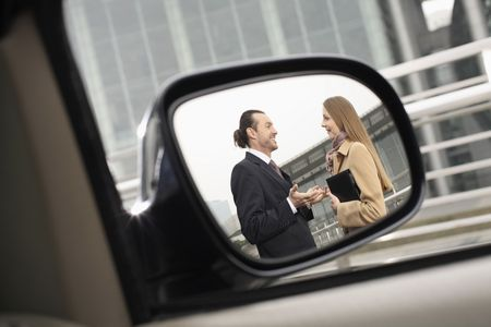 Businessman and businesswoman talking, reflected in a side view mirror photo