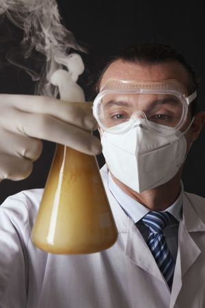 australian ethnicity: Scientist holding laboratory flask with smoke inside Stock Photo