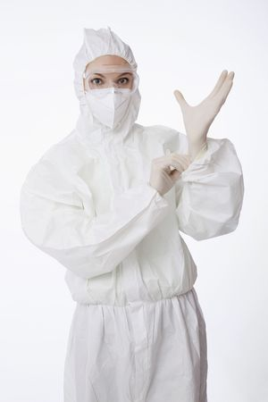 Scientist in boiler suit putting on rubber gloves photo