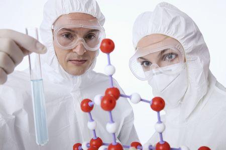 Scientists examining molecular model and liquid in test tube photo