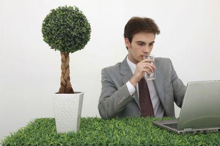 Man using laptop while drinking water photo