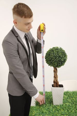 Man measuring height of potted plant photo